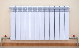 Radiator. A radiator, pipes and taps Royalty Free Stock Photos