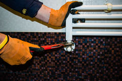 Radiator repairing with a wrench in bathroom. Workers repaired damaged radiator in a new bathroom Stock Image