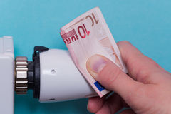 Radiator thermostat, banknote and hand - blue Royalty Free Stock Images