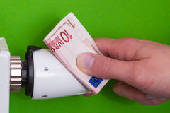 Radiator thermostat, banknote and hand - green Stock Photos