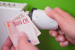 Radiator thermostat, banknote and hand - green Royalty Free Stock Image