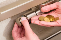 Radiator thermostat, coins and hand Royalty Free Stock Images