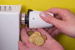 Radiator thermostat, coins and hand - yellow Stock Photo