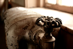Radiator valve. A radiator valve near a bright window ledge is a grim reminder of winter heating bills Stock Image