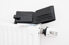 Radiator and wallet. Heating costs concept with a black wallet on a radiator Royalty Free Stock Photos
