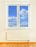 Radiator and window with blue sky view Royalty Free Stock Photos