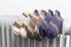 Radiatore di olio che asciuga tre paia dei calzini colourful su fondo bianco fotografie stock