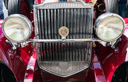 Radiatori and headlights of a classic burgundy red Packard sports car