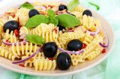 Radiatori för pastasallad med höna, svarta oliv, blå lök, söt peppar på en vit träbakgrund royaltyfri foto
