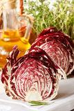 Radicchio. Two half radicchio lettuce on a white kitchen board Royalty Free Stock Photography