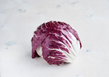 Radicchio red salad on wooden background. Horisontal. Radicchio red salad on white wooden background Royalty Free Stock Image
