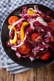Radicchio salad with tomatoes and sweet peppers closeup. Vertica. Radicchio salad with tomatoes and sweet peppers closeup on a plate. Vertical view from above Stock Image