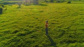 Radiellt flyg för låg höjd över sportyogaman på perfekt grönt gräs Solnedgång i berg arkivfilmer