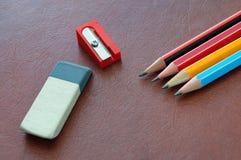 Radiergummi, Bleistifte und einen Bleistiftspitzer lokalisiert auf ein braunes BAC schreibend Lizenzfreie Stockfotos