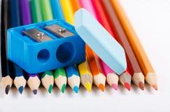 Radiergummi, farbige Bleistifte und Bleistiftspitzer auf weißem Hintergrund Stockfotos