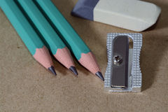Radiergummischreibensbleistifte und -bleistiftspitzer auf Kraftpapier Stockbilder