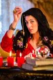 Radiesthesist in Seance dowsing with pendulum. Fortuneteller radiesthesist in Seance dowsing with pendulum telling the future Stock Image