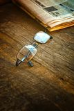 Rading glasses and newspaper Stock Images
