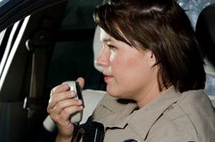 Radio call. A female police officer talks on the radio while sitting in her patrol car Stock Images