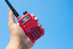 Radio communication in hand. Red radio communication device hold on man hand Royalty Free Stock Photo