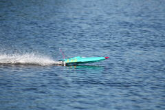 Radio controlled speedboat. Small blue radio controlled speed boat on the water Stock Image