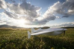 Radio controlled toy plane in the grass. Radio controlled toy airplane in the grass with a cloudy blue sky and sun rays stock image