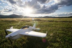 Radio controlled toy plane in the grass. Radio controlled toy airplane in the grass with a cloudy blue sky and sun rays stock images