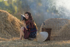 Radio d'ascolto della bella donna locale asiatica su paglia Fotografie Stock Libere da Diritti