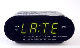 Radio d'horloge avec le mot TARD Photo stock