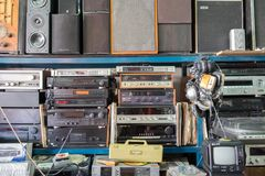 Radio del vintage, receptores, TV, altavoces y otros viejos dispositivos electrónicos en los estantes de una tienda del mercado d imagen de archivo libre de regalías