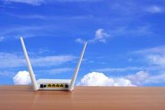 Radio del wifi del router del módem en piso de madera con el fondo del cielo azul fotos de archivo