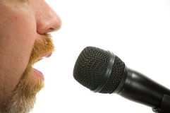 Radio DJ. Bearded man speaking into a microphone with only nose, cheeks and mouth visible. Isolated on white background Stock Photography