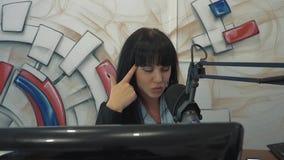 Radio DJ en el estudio de la difusión La muchacha pone un finger a su cabeza, representando cansancio almacen de metraje de vídeo