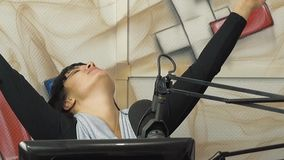 Radio DJ nello studio di radiodiffusione La ragazza mette un dito alla sua testa, rappresentante l'affaticamento archivi video