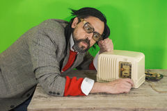 Radio Dumb on Table. An untidy bizarre man, wearing big patched glasses and a toupee, listening to a radio station on an antique bakelite tube radio on scratched Royalty Free Stock Images