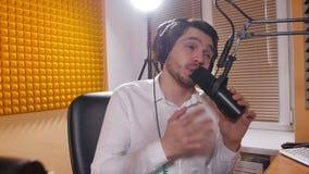 Radio e concetto di radiodiffusione in tensione Giovane con le cuffie che parla sul mic, radio online stock footage