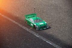 Radio-gecontroleerde groene auto op een asfaltspoor, close-up, competities in radio-gecontroleerde autosport, kampioenschap stock foto's