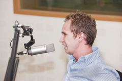 Radio guy. Young Caucasian male in front of the microphone at the radio station, general concept, interview, speaker, DJ Royalty Free Stock Photography