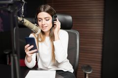 Radio host communicating on air in studio. Young hispanic female host communicating on microphone in radio studio with headphones and mobile phone Stock Photo