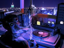 Radio host at night. Interior of a radio station, by night with view on the city. The radio host is having a break at the time that he listens to the music that stock photo