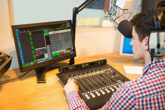 Radio host operating sound mixer while looking in monitor Stock Image