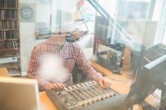 Radio host operating sound mixer in studio Stock Images