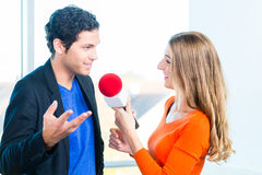 Radio host in radio stations with interview. Female Radio host doing interview with Studio guest in radio station during a show for radio live in the Studio Stock Photo