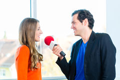 Radio host in radio stations with interview. Female Radio host doing interview with Studio guest in radio station during a show for radio live in the Studio Royalty Free Stock Photo