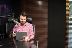 Radio presenter taking on air interview. Radio host sitting with a clipboard and talking on microphone in studio Royalty Free Stock Photos