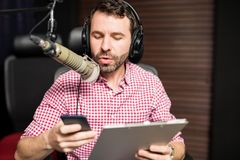 Radio host using mobile during on air interview. Handsome young latin man working as radio host at radio station sitting in front of microphone holding clipboard Royalty Free Stock Images