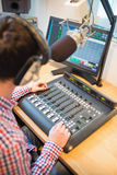 Radio host using sound mixer on table Royalty Free Stock Image