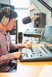 Radio host wearing headphones operating sound mixer Royalty Free Stock Photo