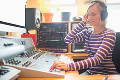 Radio host wearing headphones using sound mixer Stock Photos