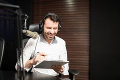 Radio jockey interviewing a guest from studio. Handsome young male radio host with headphone sitting in front of a microphone interviewing a guest holding royalty free stock photos